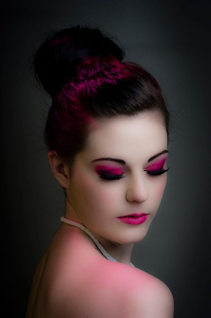 Dramatic model headshot with heavy pink make up and pink hair light.
