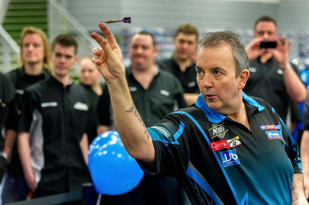 Phil 'The Power' Taylor gives tips to a local pub darts team at JJB sports.
